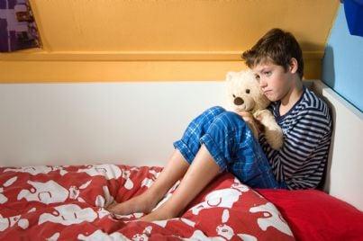 ragazzo triste seduto nella sua stanza sul letto