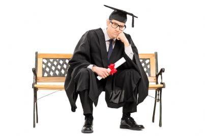 ragazzo laureato triste in panchina