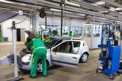 meccanico in officina che effettua revisione auto