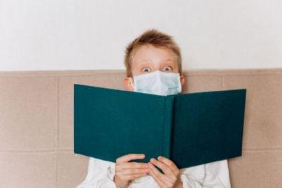 bambino con mascherina legge libro