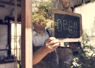 uomo mette cartello aperto nel negozio