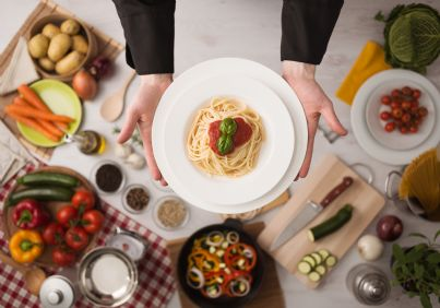 primo piano di piatto professionale e sullo sfondo varie pietanze