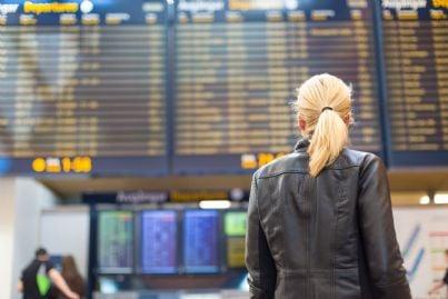 donna che guarda tabellone orari partenze aerei