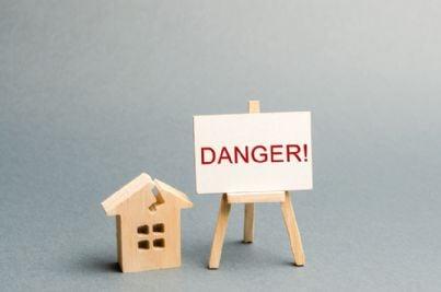 casa in rovina con segnale pericolo