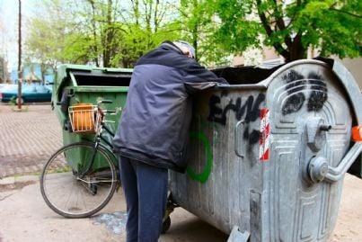 senzatetto che fruga tra i cassonetti per rubare rifiuti