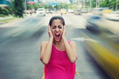 donna grida e si copre le orecchie per il forte rumore