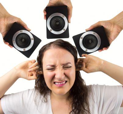 donna che si protegge dai rumori di altoparlanti
