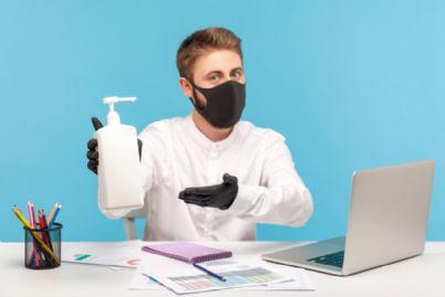 uomo in ufficio mostra sanificazione per coronavirus