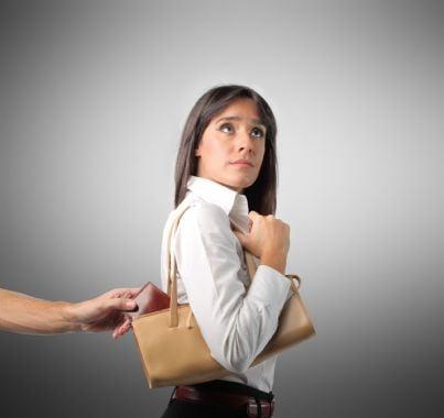 mano che scippa portafogli dalla borsa di una donna