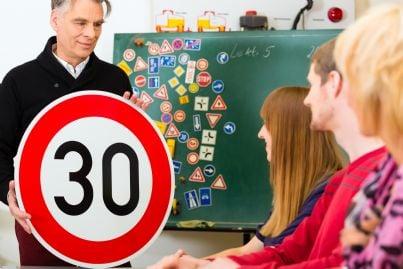 istruttore di scuola guida con segnali e studenti