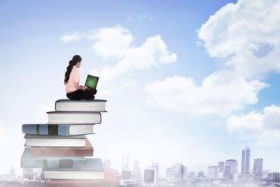donna con computer su una cima di libri guarda carriera futura