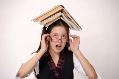 ragazza occhiali con libri di scuola sulla testa