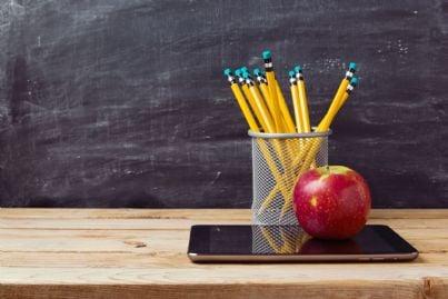 matite scuola su un tablet con sullo sfondo una lavagna