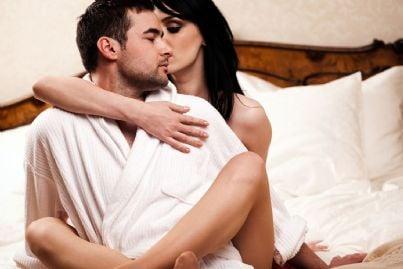 Coppia di amanti distesa seduti su un letto