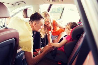 genitori sorridono alla propria bambina seduta nel seggiolino in auto