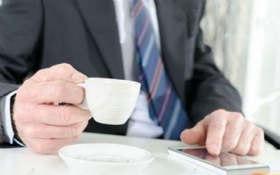 Uomo con smartphone e caffe