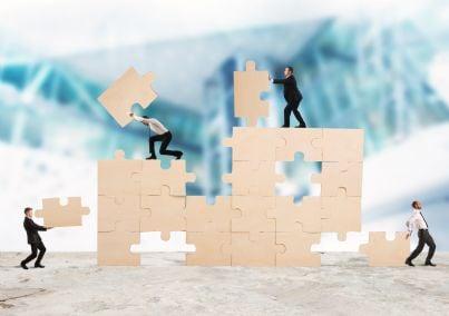 uomini al lavoro per costruire un puzzle aziendale