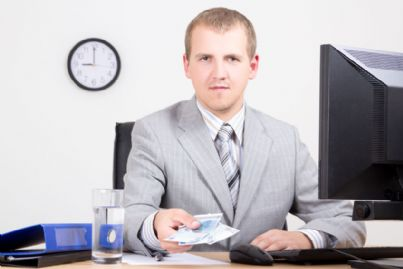 uomo che mostra soldi in ufficio
