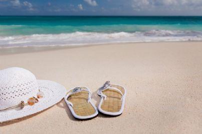 Ciabatte da mare e cappello posate sulla spiaggia