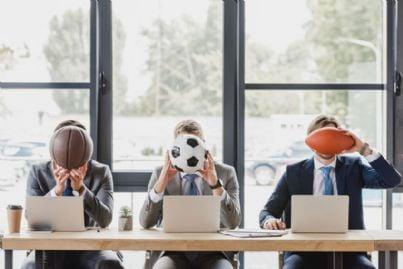 uomini in ufficio che mettono palloni davanti alla faccia
