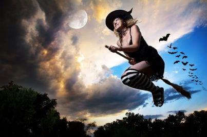 una strega che vola sulla scopa nel cielo