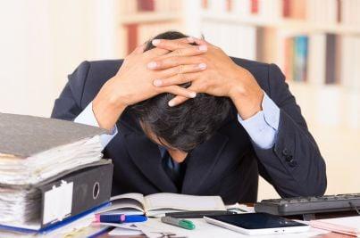 Uomo stressato dietro una scrivania