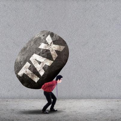 un uomo porta un macigno con sopra scritto tasse