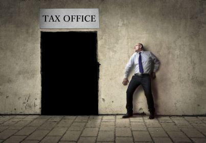 uomo che ha paura di entrare in ufficio tasse