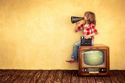 bambino su un televisore con megafono simbolo comunicazione