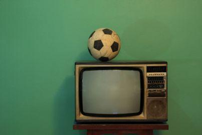 vecchio televisore con sopra pallone da calcio