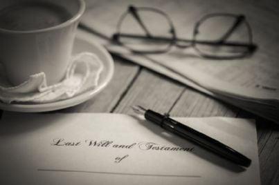 scrivere testamento su un tavolo con occhiali e penna