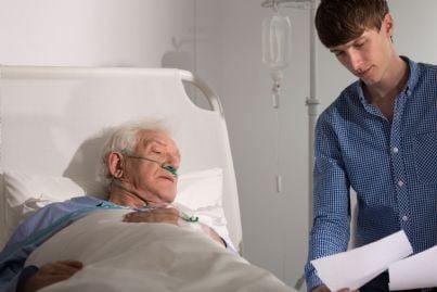 uomo anziano che firma davanti a nipote testamento biologico