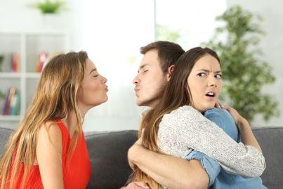 uomo abbraccia donna con amante dietro