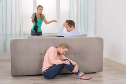 moglie che scopre tradimento con amante nascosta dietro divano