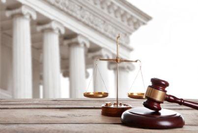 bilancia giustizia e martello con alle spalle un tribunale
