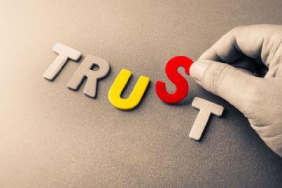 mano che compone puzzle con parola trust