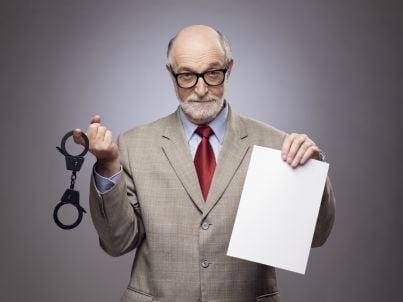 uomo anziano con manette e contratto in mano