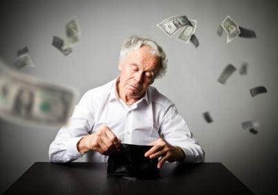 uomo anziano e portafogli vuoto con soldi che volano via