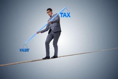uomo in equilibrio tra tasse e debiti