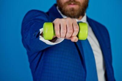 uomo che tiene in mano un peso come simbolo della sua fatica negli affari