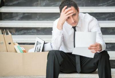 uomo triste che legge lettera di licenziamento