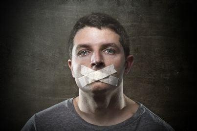 uomo con cerotto sulla bocca per censura