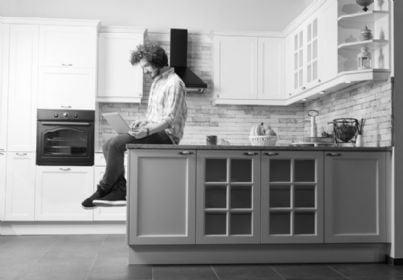 uomo seduto in cucina beve un caffe e lavora al computer