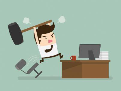 uomo arrabbiato colpisce con martello un computer