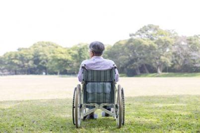 uomo anziano disabile su una sedia a rotelle