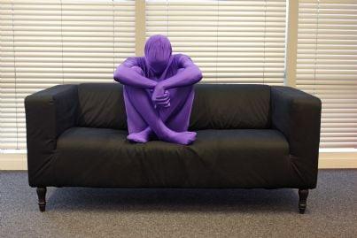 uomo travestito sul divano in totale solitudine