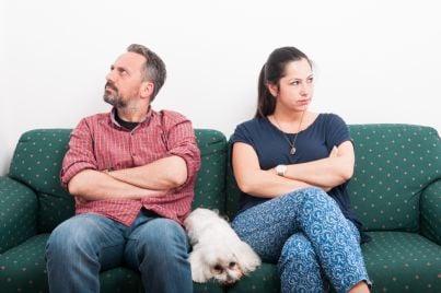 uomo e donna in lite sul divano divisi dal cane
