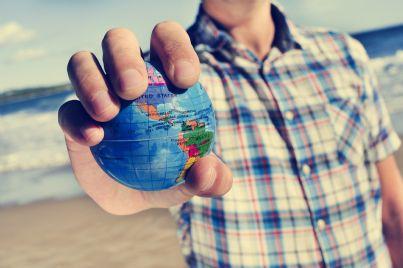migrante tiene in mano globo terrestre