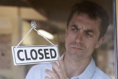 uomo chiude negozio per crisi