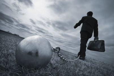 uomo con palla al piede si allontana con valigetta in mano
